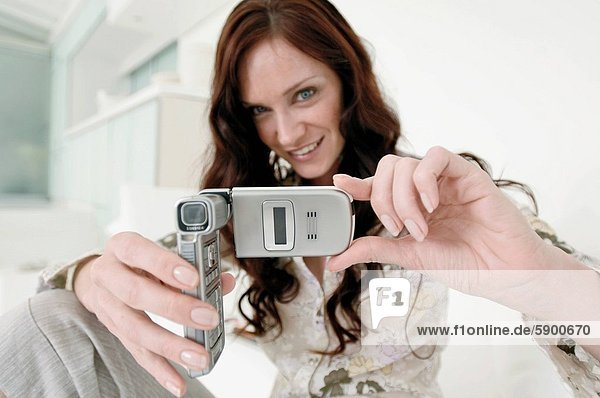 Portrait of a mid adult woman taking a picture with a mobile phone and smiling