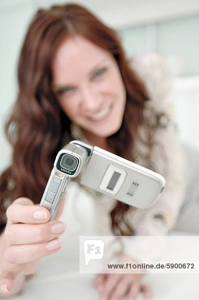 Mid adult woman taking a photograph with a mobile phone and smiling