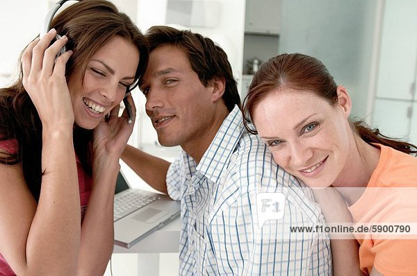 Close_up of a young woman listening to music with a young man and another young woman smiling beside her