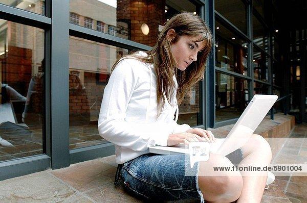 Seitenansicht einer jungen Frau arbeiten auf einem laptop