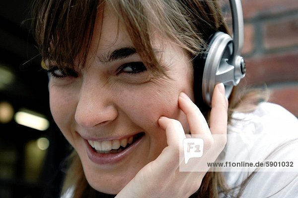 Close_up of a young woman wearing headphones and listening to music