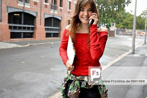 Portrait einer jungen Frau Gespräch auf einem Mobiltelefon und lächelnd
