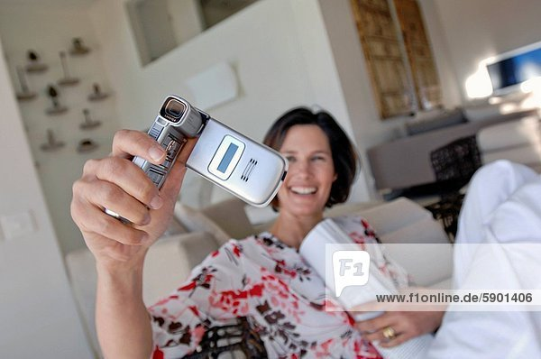 Close_up of a mature woman taking a photograph of herself with a mobile phone
