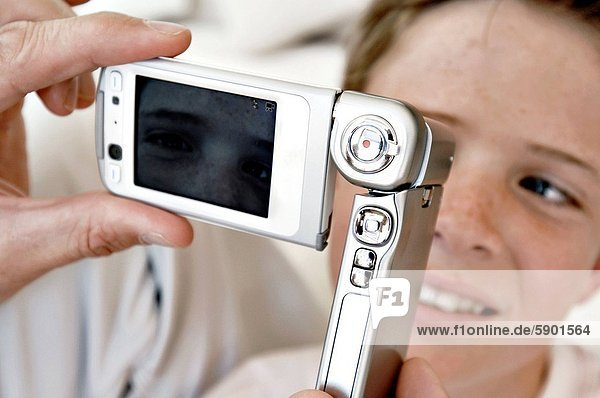 Close_up of a persons hand taking a photograph of a boy with a mobile phone
