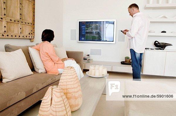 Handy  benutzen  Frau  Mann  sehen  Fernsehen  reifer Erwachsene  reife Erwachsene  Kurznachricht