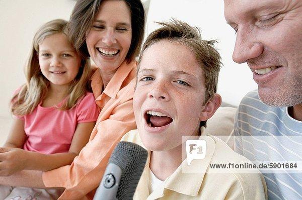 sitzend  nebeneinander  neben  Seite an Seite  Portrait  Junge - Person  Gesang  Mikrophon