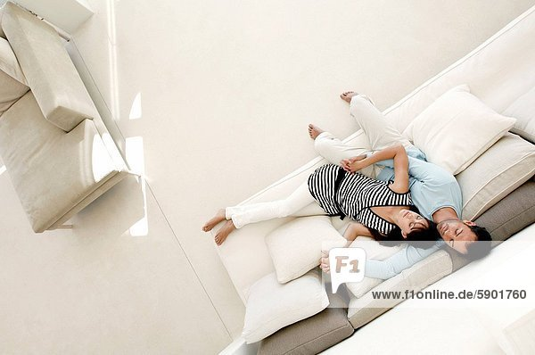 High angle view of a young couple sleeping on a couch