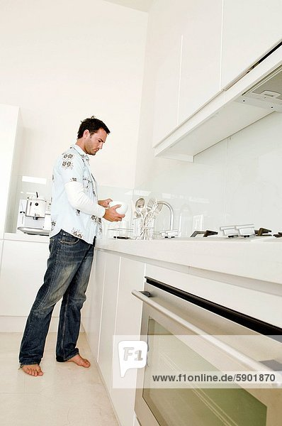 Side profile of a young man standing at a kitchen counter and washing a bowl