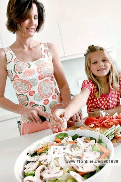 Frau  schneiden  Gemüse  Scheibe  reifer Erwachsene  reife Erwachsene  Tochter  aufheben