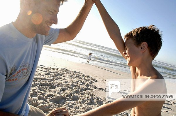 Side profile of a boy playing with his father on the beach