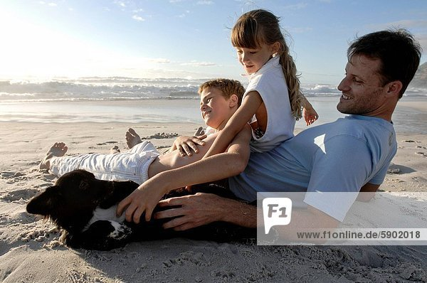 Side profile of a mid adult man sitting with his children and playing with a dog on the beach