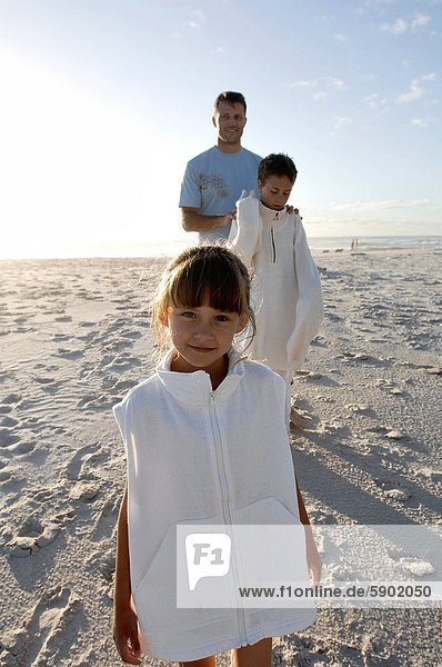 Portrait of a girl standing on the beach with her father and brother standing behind her