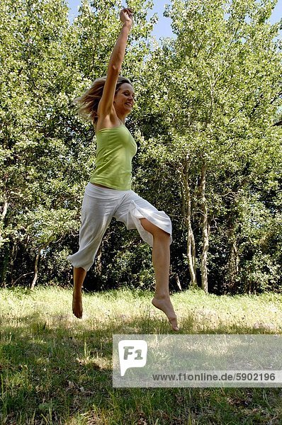 Side profile of a mid adult woman jumping in a park