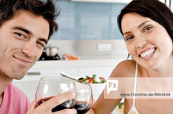 Portrait of a young couple toasting with wine glasses at the kitchen counter