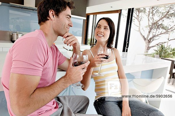 Young couple holding glasses of red wine and smiling