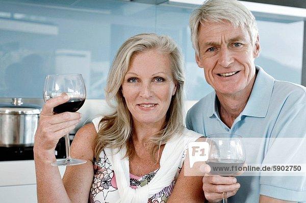 Senior  Senioren  Portrait  lächeln  Wein  Küche  halten  rot