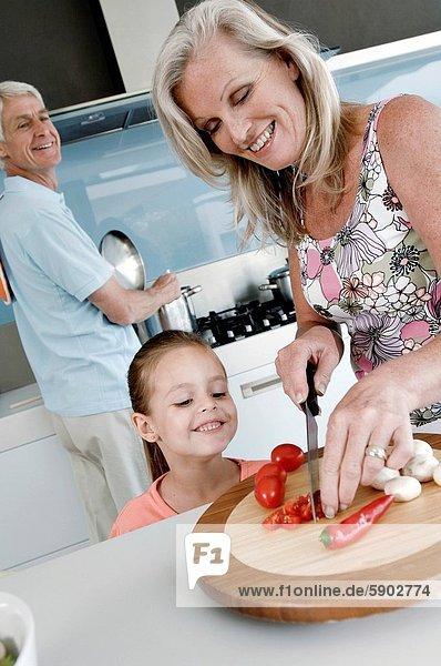 stehend  nebeneinander  neben  Seite an Seite  Senior  Senioren  Frau  schneiden  Gemüse  Enkeltochter