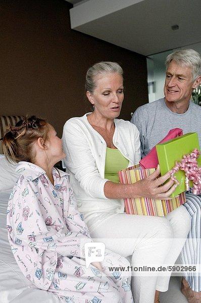 Geschenk  sitzend  nebeneinander  neben  Seite an Seite  Senior  Senioren  Frau  Mann  halten  Enkeltochter