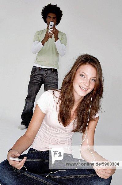 Handy  hinter  benutzen  Portrait  Frau  Mann  zuhören  Spiel  Kurznachricht  jung  MP3-Player  MP3 Spieler  MP3 Player  MP3-Spieler