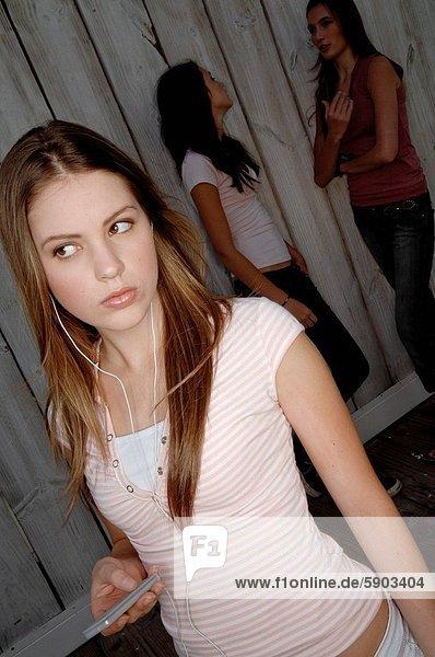 hinter stehend junge Frau junge Frauen Frau zuhören Spiel 2 jung MP3-Player MP3 Spieler MP3 Player MP3-Spieler