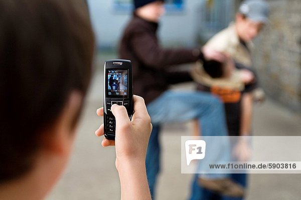 Close_up of a teenage boys hand taking a photograph of three teenage boys fighting