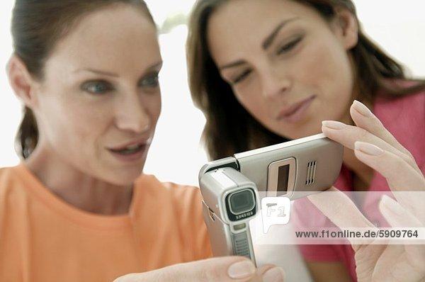 Nahaufnahme der zwei jungen Frauen Blick auf einem Mobiltelefon