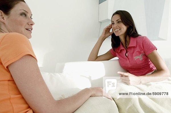 sitzend  Frau  lächeln  2  jung  Couch