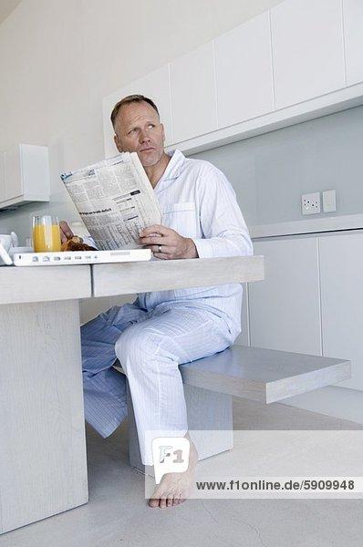 sitzend Mann halten reifer Erwachsene reife Erwachsene Tisch Zeitung