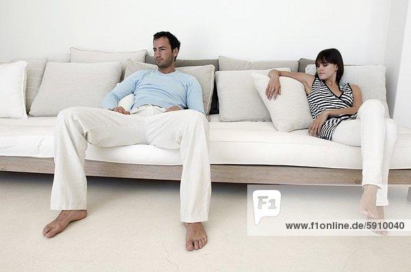 Junges Paar auf Sofa mit Teddybär