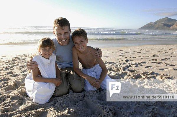 Portrait  Mann  kniend  lächeln  Strand  Mittelpunkt  2  Erwachsener
