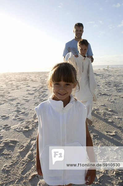 Portrait of a girl smiling with her father and brother standing behind her on the beach