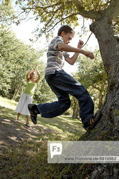 Side profile of a boy climbing a tree with his mother applauding him in the background