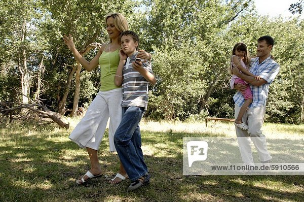 Mid adult couple walking with their children in a park