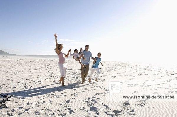 Eltern toben mit Kindern am Strand