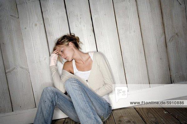 sitzend junge Frau junge Frauen sehen Boden Fußboden Fußböden Nachdenklichkeit