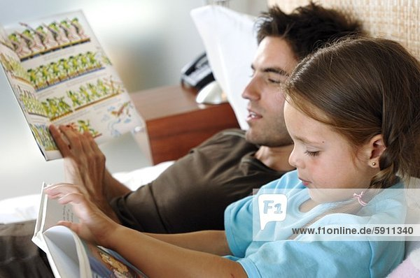 Close-up of a girl and her father reading books
