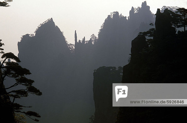 Silhouette of hills and trees at dusk  China
