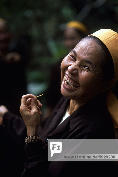 Portrait of a mature woman holding a toothpick and laughing  Vietnam