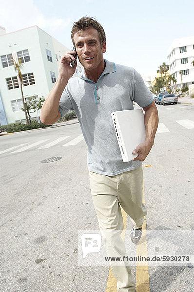 Handy  Mann  sprechen  Notebook  rennen  halten  Mittelpunkt  Kurznachricht  Erwachsener