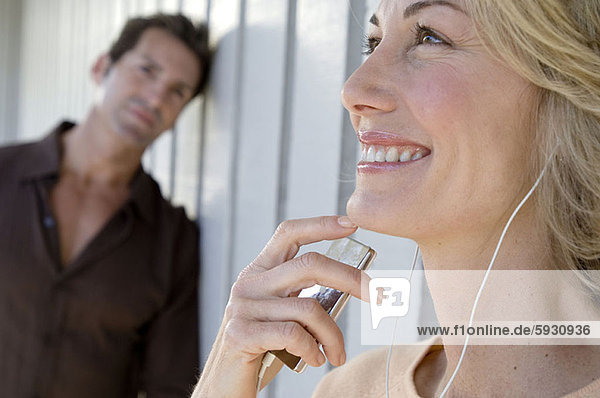 Close-up of a mid adult woman listening to music on headphones with a mid adult man standing behind her. Close-up of a mid adult woman listening to music on headphones with a mid adult man standing behind her