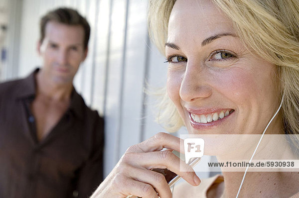 Portrait of a mid adult woman listening to music on headphones with a mid adult man standing behind her. Portrait of a mid adult woman listening to music on headphones with a mid adult man standing behind her