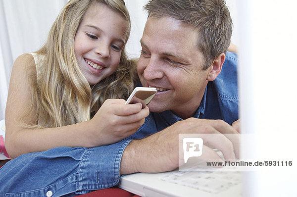 benutzen  Notebook  Menschlicher Vater  halten  Spiel  MP3-Player  MP3 Spieler  MP3 Player  MP3-Spieler  Mädchen