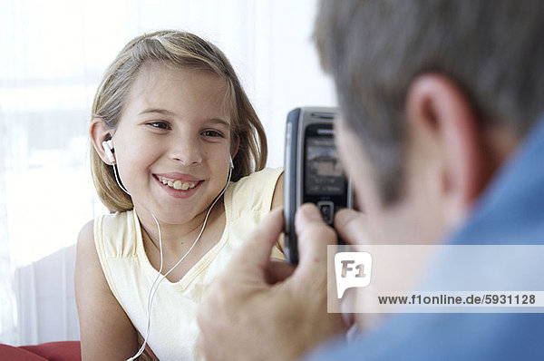 Close-up of a mid adult man photographing his daughter with a mobile phone. Close-up of a mid adult man photographing his daughter with a mobile phone