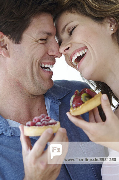 Close-up of a young couple smiling and holding pastries. Close-up of a young couple smiling and holding pastries