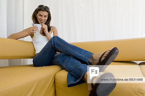sitzend  Portrait  Frau  Tasse  halten  jung  Couch  Wegwerfartikel