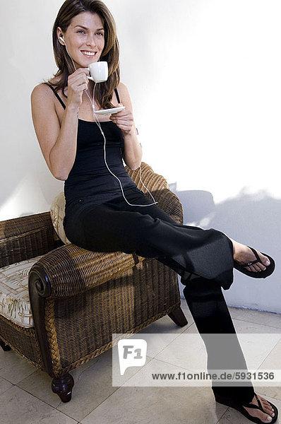 Frau  zuhören  Tasse  halten  Spiel  jung  MP3-Player  MP3 Spieler  MP3 Player  MP3-Spieler  Tee