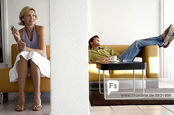 liegend  liegen  liegt  liegendes  liegender  liegende  daliegen  Frau  Mann  zuhören  Spiel  Mittelpunkt  Couch  MP3-Player  MP3 Spieler  MP3 Player  MP3-Spieler  Erwachsener  zurücklehnen