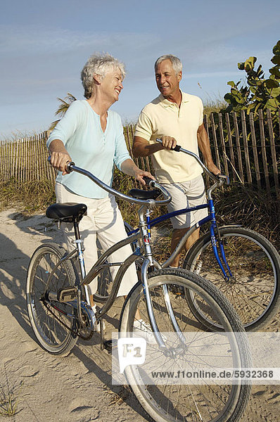 Senior couple holding bicycles and walking. Senior couple holding bicycles and walking