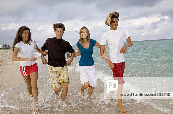 Jugendlicher  Strand  Junge - Person  rennen  halten  2  Mädchen
