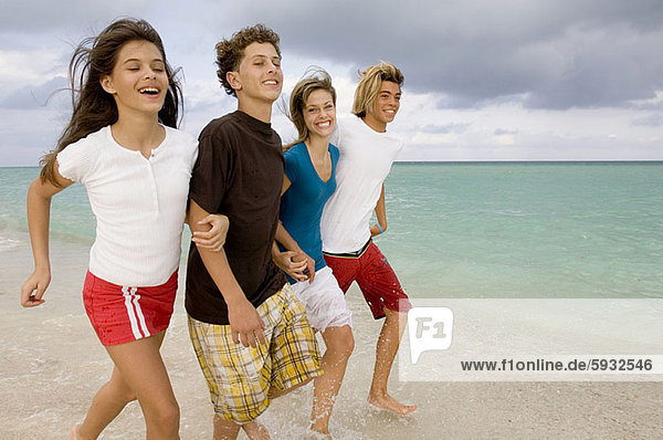 Two teenage boys and two teenage girls holding hands and running on the beach. Two teenage boys and two teenage girls holding hands and running on the beach